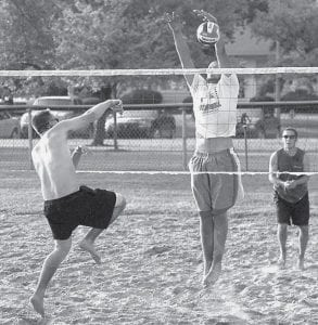 Joel Ruffer, Archbold, blocks the spike of Paul Iott, Whitehouse, in the Carp Festival three-on-three sand volleyball tournament, Friday, July 11. The block gave Ruffer's team a 25-24 victory in pool play; however, Iott's team beat the team of Ruffer, Galen Nofziger, and Glenn Nofziger 25-23 in the final to win the tournament.- photo by  Mary Huber