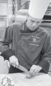 Aaron Weible, executive chef at Stella Blue, Archbold's newest restaurant, is at work in the kitchen. A graduate of the Pennsylvania Culinary Institute, Pittsburgh, he's using locally-grown meats and produce to prepare meals. He is a graduate of Tinora High School.- photo by Nanette Buehrer