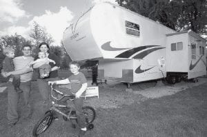 Chad and Patricia Nicholls and the fifth-wheel camper Chad built. It features an elaborate audio and video system, which includes six flat-panel televisions. From left: son Blaine, 3; Chad; Patricia holding Cora, 10 months; and Mason, 6.-  courtesy        photo