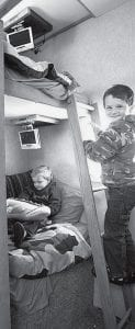 The Nicholls boys, inside the camper their father built. Note that each bunk has its own flatpanel TV, each with its own DVD player. Blaine, 3, is in his bunk; six-year-old Mason is on the ladder.-  courtesy photo