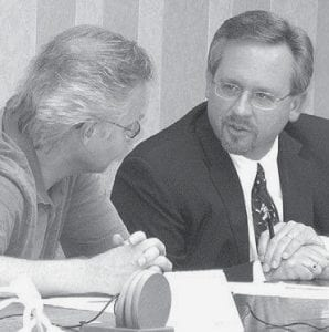 Denny Meyers, left, and Jim Wyse, members of the Archbold Planning Commission, discuss whether or not a conditional use permit is required for a home for developmentally disabled persons, including those with mental retardation, on Sylvanus Street.-  photo by David Pugh