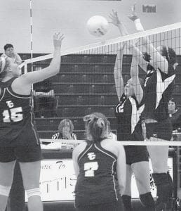 Stacey King (12) and Haley Nofziger (7) team up to block Bethany Critchley's spike in the second game of Pettisville's sectional final win over Toledo Christian, Saturday, Oct. 18.-  photo by Mary Huber