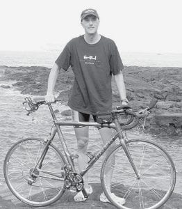 Brian Schweinhagen stands on lava formations on the coast of Kona, the Big Island of Hawaii. After 13 years of entering, Schweinhagen got the chance to participate in the Ironman Triathlon, held annually on the island. He's shown her with his racing bike. Bikes for serious Ironman contenders cost anywhere from $3,000 to $12,000, he said.-  courtesy photo