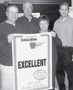 Sue Westendorf, of the State Board of Education, third from left, presents a banner recognizing the Pettisville Local School District for five years of excellent ratings on the Ohio Department of Education school report card. School board members accepting the award are, from left, John King, president; Dan Bruner, vice president; and Daniel Sauder. -  courtesy photo