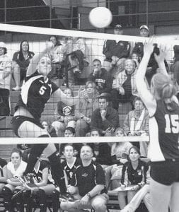 Katie Weber (5) spikes over the outstretched arms of Leipsic's Shannon Nadler. Weber was 18/21 in attacks, including six kills.-  photo by  Mary Huber