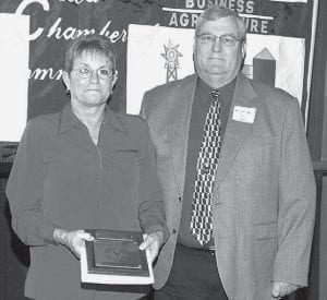 Carol Grime, Carol Ann's City Café, receives a plaque from Ken Miller, incoming Archbold Area Chamber of Commerce president, recognizing 10 years in business.