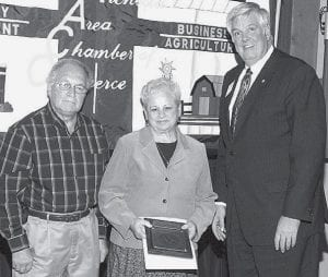 From left, Marv and Sharon Lantz, Candy Cane Christmas Shop, receive a 10-year award from Paul Siebenmorgen, outgoing chamber president.