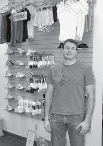 Kyle Brodbeck, president of Locker Room, Inc., stands in the new Locker Room Essentials retail area. Brodbeck said the company's decision to open additional retail space is a vote of confidence in downtown. To keep retail going in a small community,