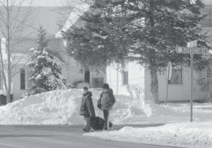Council continued a discussion about sidewalk snow-shoveling at its Monday, Feb. 2 meeting. However, snow piled high at intersections is another concern. Two students walking home after school had no choice but to walk in the street, Friday, Jan. 30. A mountain of snow plowed from village streets blocked shoveled sidewalks at the northwest corner of Park and Pleasant streets. The snow was nearly as tall as the boys.- photo by Mary Huber
