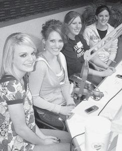 At left: Archbold High School cheerleaders, Emily Grisier, Laci Gautsche, Nichole Short, and Rachel Kelley, from left, in the radio studio of WMTR during the 35th annual Fulton County Heart Radiothon. At right, Bryce Williams, 9, Archbold, plays a game at the Fairlawn Haven Heart Carnival. Both events were held Thursday, Feb. 12.-  photos by David Pugh