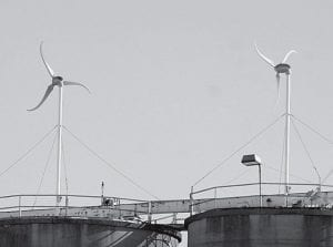 Two wind turbines stand atop the Pettisville Grain Company elevator in Pettisville. The company took advantage of a government grant to purchase the turbines, which cost about $11,000 each. Company officials expect the turbines to pay for themselves in electricity savings in about four years.- photo by David Pugh