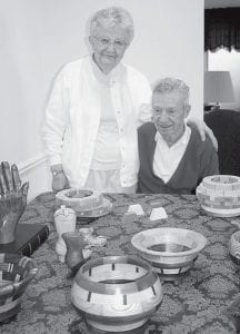 Helen (left) and Lauren Bowman, who live in the Fairlawn duplexes, with some of the wooden bowls and carvings he sculpts. He has donated several of his works to the Fairlawn Auxiliary Auction, but Helen reports her homemade pies bring more money.- photo by  David Pugh