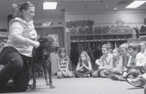 Archbold elementary school students watch Andrea M. Christenson, Fayette, demonstrate how her service dog, Coco, helps her get up from the floor. Christenson has Adult Onset Stills Disease, a rare form of arthritis. Coco was a stray her family adopted. Christenson trained Coco to assist her. Christenson and Coco visited the school Friday, March 27. - photo by David Pugh