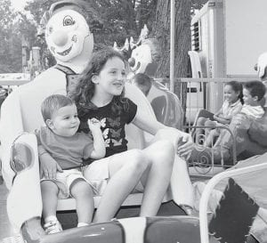 Trenton Fetter, 18 months, Adrian, Mich., and cousin Jordan Skates, 9, Pettisville, ride with the clowns at the Fulton County Fair. They are the grandchildren of Charles and Laura Nafziger, Pettisville.- photo     by Mary Huber