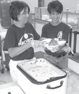 Danielle Wyse, left, and Shelly Grosjean, of the Archbold Athletic Boosters Club, load up a plate with food during the group's fall sports rally and chicken barbeque. The event was held at Archbold High School, Friday, Sept. 11, prior to the Streaks' home football game with Fairview.– photo by David Pugh