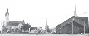 Two of the three church buildings on the St. John property at the intersection of St. Rt. 66 and US 6 can be seen in this photo. They are, far left, the 1898 church, and far right, the current sanctuary, completed over 100 years later in 2007. The 1898 church is 90 feet tall at the top of the steeple, said to be one of the highest points in Henry County. Even though the 1898 building was moved north 30 feet in 1957 to accommodate a rerouting of US 6, the front step of the church is still on the highway right-of-way. Not visible in the photo is the third church, a small white building constructed in 1861. It was later added to the back of the 1898 church and used as a Sunday School.– photo by David Pugh