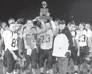 Kenny Cowell, Archbold Lions Club president, presents the Lions Club trophy to seniors on the AHS football team. The Streaks defeated Wauseon 31-24 to keep the trophy in Archbold. The 12 AHS seniors include, from left: Josh Penrod (83), Jarett Wyse (67), Cameron Yontz (73), Adam Heaston (55, partially hidden behind Cowell), and Collin Walker (23), as well as Josh Meyers, Trey Westrick, Tyson Flores, Drew Smith, Jackson Gerken, Nate Hammersmith, and Jacob Badenhop.– photo     by Scott Schultz