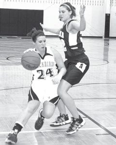 Above: Blue Streak Hailey Galvan, right, blocks Kylee Garcia's path to the basket. Galvan had a number of blocked shots in the contest with Pettisville, which Archbold won 62-49. Galvan was also the game's top scorer, with 20 points. At left: Erica King (32) is fouled by Betsy Wyse (11) with 1:54 left in the second period. King led PHS with 17.–photos by Scott     Schultz