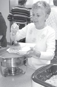 Kathy Higbea, Defiance, ladles gravy onto chicken pie during the Ridgeville American Legion Auxiliary annual Chicken Pie Dinner, Sunday, Feb. 21. The event, which dates over 100 years, is held on the third Sunday in February.–photo by David Pugh