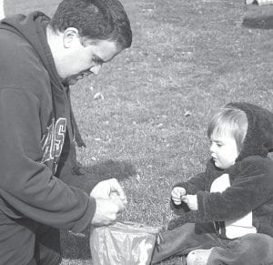 Nick Rice, Pettisville, helps daughter Ashalyn, 18 months, go through the plastic eggs she collected during the Pettisville Easter Egg Hunt, Saturday, March 27, at Pettisville Park. Weather was chilly, but clear. The event was sponsored by the Pettisville High School student council. The Archbold Flashlight Easter Egg hunt, postponed due to bad weather, is tomorrow, Thursday, at Ruihley Park.– photo by Deb Neueneschwander