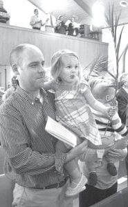 Miley Gericke, 2, holds a palm frond, part of a Christian tradition marking Palm Sunday, during services at St. Martin's Lutheran Church, Sunday, March 28. She is held by her father, Zach. In the Christian faith, palm branches commemorate the arrival of Jesus in Jerusalem prior to his crucifixion, when crowds laid palm fronds in his path as he rode into town on a donkey.–photo by David Pugh