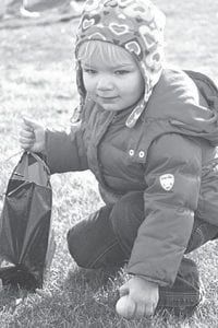 Ava Genter, 2, Archbold, picks up an Easter egg during the Pettisville Easter Egg Hunt, Saturday, March 27 at the Pettisville Community Park.– photo by D.J. Neuenschwander
