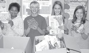 Eryka Wallace, Stuart Yoder, Amber Klopfenstein and Jaelyn Rufenacht, sixth graders at Pettisville, from left, display some items Maggie Enderle's fifth- and sixth-grade classes are collecting as part of Terra Cycling, a program that turns things like empty food wrappers and cereal boxes into consumer products. The class receives two cents per wrapper, and has accumulated $90 so far. Enderle said the project demonstrates to students that with a little effort, waste can be kept out of landfills. The project has been ongoing for weeks, not just on Earth Day.–photo by David Pugh