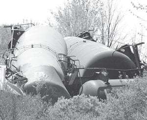 Tank cars, each loaded with 30,000 gallons of ethanol, lie stacked together after a derailment on the Norfolk Southern main east-west line, Monday, April 19, in Williams County, near the community of Melbern. Leaking ethanol formed a vapor cloud, which prompted emergency responders to call for the evacuation of area homes for a few hours. There were 89 cars in the eastbound train, 39 of which derailed. Seven tank cars leaked. An investigation into the mishap is ongoing.–photo by  Jennifer J. Hellard, used with permission of the Bryan Times