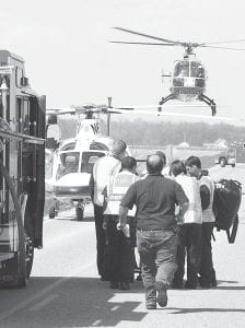 A crash between a commercial dump truck and a pickup Wednesday, April 21, at the intersection of US20A and Co. Rd. 22 sent two people to Mercy St. Vincent Medical Center. Top: Archbold Rescue workers prepare to load a victim aboard a helicopter ambulance; in the background, another helicopter ambulance lands for the second victim. Below: Richard and Judy Whaley, Fayette, were riding in this pickup when the crash occurred. Both have since been released from St. Vs.– photos by David Pugh