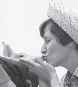 "Top left: To thunderous chants of ""Kiss A Pig,"" Dorothy Lambert, Archbold Elementary School principal, kisses a pig during a special assembly closing Right To Read Week, Friday, May 14. The week's theme was ""Down On The Farm."" Lambert challenged students to ready 46,000 minutes from Monday to Friday; if they did, she promised that she would kiss a pig. The students met and exceeded the goal, reading 54,825 minutes. Top right: Jeff Benecke, a fourth grade teacher, puckers up for a kiss. Teachers of the classes in each grade who read the most during the week learned they would be kissing the pig, too. Holding the pig is its owner, Chris Ott. Bottom left: Second graders D'Andre Lavia and Olivia Villanueva scream after finding out the reading goal was met and that Mrs. Lambert would have to kiss the pig.– photos by Mary Huber"