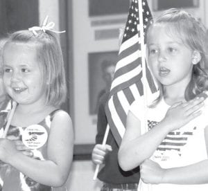 Kaylen Behnfeldt, left, and Emaleigh Heckel recite the Pledge of Allegiance at the Memorial Day program at the Ridgeville American Legion, Monday, May 31. The two participated in the children's flag drill, a tradition at the program. Both girls are from Ridgeville Corners.– photo by Mary Huber