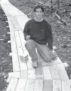 Eric Buckenmeyer kneels on the boardwalk of treated pine he and other volunteers constructed through Goll Woods to keep hikers out of the mud on one of the trails. Buckenmeyer took on the $3,000 project to build a boardwalk and lay gravel on other trails to fulfill one of the requirements to earn the rank of Eagle Scout.– photo by Alicia Buckenmeyer
