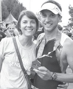 """Jesse Sensenig, right, with his wife, Amanda, after completing the Iron Man Triathlon event in Madison, Wis., last month. Amanda wears a """"Team Sensenig"""" T-shirt, which was worn by family members who traveled to Wisconsin to see Jesse race. Jesse said his wife was supportive of his decision to compete, """"though she thought I was kind of nuts."""" –courtesy photo"""