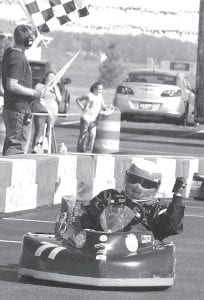 """John Huffman, veteran Archbold kart racer, raises his fist in victory after winning a heat race in the stock 400 class during kart racing action in Archbold, Sunday, Oct. 10. Three local racers won feature races at the event: Dean Sauder, Archbold, won the over 35 class; Jeremy Mann, 15, Archbold, won the junior stock feature event; and Logan Wyse, Findlay, formerly of Archbold, won the stock medium feature. A total of 76 karts turned out. Competition was stiff. """"Just about everyone was a track champion somewhere,"""" Huffman said. –photo by David     Pugh"""