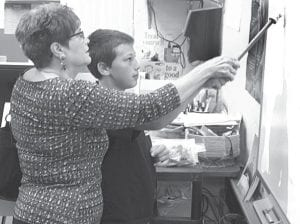 Above: Peg Lauber, Wauseon, grandmother of Gavin Grime, a fifth grader, work at a smart board during the Archbold Middle School Grandparents Day, Friday, Oct. 8. Below: Molly Conway, a fifth grader, left, with her grandparents Jack Conway, Dallas- Ft. Worth, Texas, and Linda and Bob Fetter, Defiance.–photos      by David Pugh