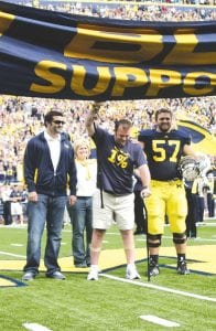 """Brock Mealer, center, reaches up to touch the """"Go Blue"""" banner at the University of Michigan Sept. 4 home opener in Ann Arbor, Mich. After a spinal cord injury suffered in an auto accident, he was given little hope of ever walking again. With the help of canes, he walked across the field at Michigan Stadium to lead the UM football team onto the field. At his left is his brother, Elliot, a UM player; to his right is his brother, Blake. Behind him is his mother, Shelly.–photo by Scott Schultz"""