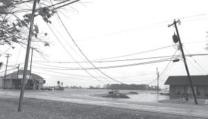 High winds damaged utility poles throughout Fulton County Tuesday, Oct. 26, including this one on St. Rt. 66 at the St. Rt. 2 intersection north of Archbold. The low-hanging lines blocked the roadway. Fulton County Sheriff Department dispatchers triggered the county tornado sirens at 11:16 am in response to a National Weather Service tornado warning, based on radar observations. The all-clear announcement was given an hour later. Other locations with damage to utility poles were Co. Rds. D and 9, N and 16-3, and E and 3. Also, a pole on the Toledo Edison high-voltage distribution line behind the ConAgra factory broke, but the wires remained intact.–photo     by Mary Huber