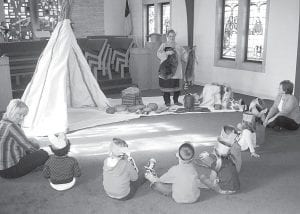Nancy Lewis, from Sauder Village, gave a talk about Native Americans to students at St. John's Christian Preschool, Wednesday, Nov. 10. Top: Joan Burkholder, far left, assistant teacher, and Linda Yaney, far right, preschool director, sit with students as Lewis gives her talk. Right: From left, Yaney and her students, Cailin Stellhorn, Tearra Taylor, and Emma Lingle listen closely. –photo by David     Pugh