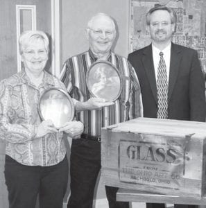 """Dale """"Fuzz"""" Taylor, center, donated a crate that was once used to ship Ohio Art Company products to the Village of Archbold. The company started in Archbold in 1908, and crates like this one are seen in photographs in which they lined North Defiance Street. The company moved to Bryan in 1912. Taylor and his wife, Marilyn, hold original Ohio Art pictures. Behind the crate is Jim Wyse, Archbold mayor.–photo b y David Pugh"""