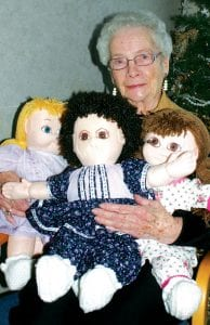 Dorothy Golden, a Fairlawn Haven resident, holds three of her Golden Child Originals dolls that she made with the help of Martha Armstrong, Fairlawn activities director. The dolls will be given to three needy children. During the 1980s and 90s, Golden made more than 700 dolls, which were sold in a Florida yard goods store. In this photo, taken last week, the dolls weren't quite ready– they needed to have their mouths attached.– photo by David Pugh