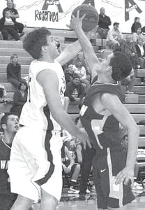 Tyson Dietrich, left, attempts to avoid the outstretched paw of a Bulldog and put up a shot. Dietrich led the Streaks with 12 points.–photo by Scott Schultz