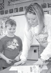 Logan Miller, a first grader at Archbold Elementary School, watches while his teacher, Andrea Thiel, looks over his writing project during the annual 100-Day celebration, Monday, Jan. 31.– photo by David Pugh