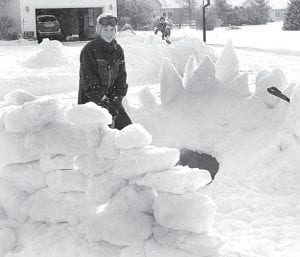 Lucas Rupp, 12, left, and Andrew Beck, 11, in the background, stand in their respective snow forts. The two live across the street from each other in Archbold and have snowball fights back and forth.– photo by Mary Huber