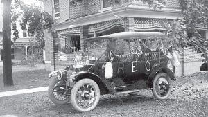 OLD PHOTO CORNER: William Huner displays patriotic decorations on his house and automobile in Ridgeville Corners in the early 1900s. The house stands today in its original condition on the Ridge Road. Huner's REO was one of the first in the village.– Antique photograph from the collection of Deb Lecklider