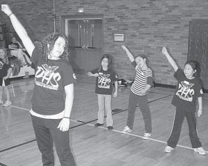 Angie Nofziger, Pettisville High School cheerleader coach, and her high school cheerleaders have been working with the Mini-Cheerbirds, elementary school students, in preparation for a special performance, Feb. 25, during the boys basketball game against Fayette. Top: Kaylee Dougherty, a varsity cheerleader, leads, from left: Karsen Pursel, first grade; Jamie Monroe and Leslie Garcia, second grade; and Meleah Plank, first grade. Right: Nofziger works with Elise Hoylman, a kindergarten student.– photos by David Pugh