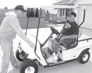 Tracey Zuver, left, talks to his father Don about the golf cart Tracey is preparing for street use. Don lost his left leg in a 1967 accident. The open design of the golf cart makes it easier for him to get in and out of the vehicle.– photo by David Pugh
