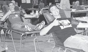 Pettisville juniors Travis Beck and Zach Pursel, from left, give the thumbs-up sign as they donate blood, Wednesday, April 27, during a student council blood drive at the Pettisville school.– photo by Mary Huber