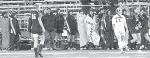Bundled-up teammates along the sidelines watch the action.