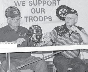 Denny Behnfeldt, left, pulls bingo numbers and hands the balls to Ted Ripke, who announces the pulled numbers during the Ridgeville American Legion Feather Party, Friday, Nov. 18. Thirty games of bingo were played that night.–photo by Mary Huber