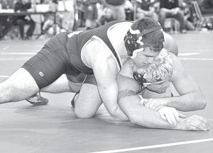 Blue Streak senior Kellen Seaman, on top, works his opponent at the Div. III district meet. Seaman finished sixth after working his way through the consolation rounds. He finished the season with a 35-29 record.– photo by Mario Gomez